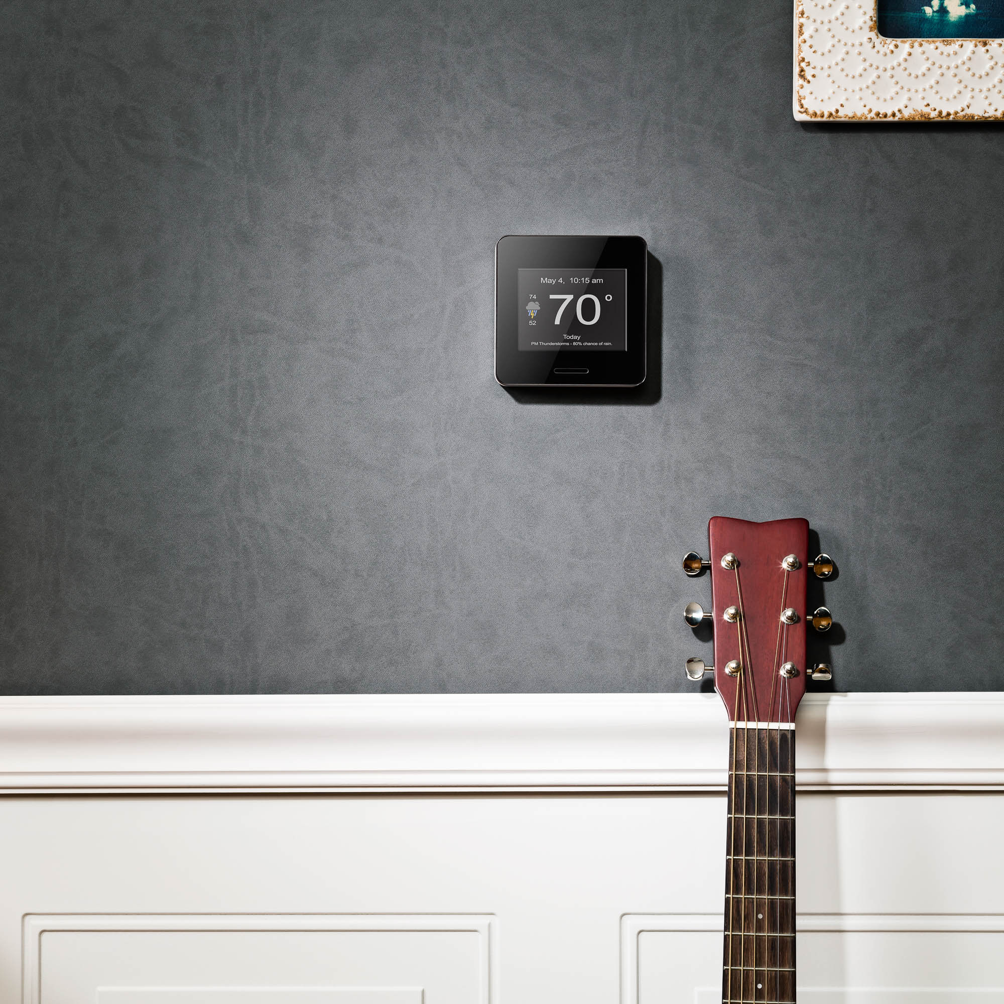 lifestyle photography of wifi weather station in living room with guitar
