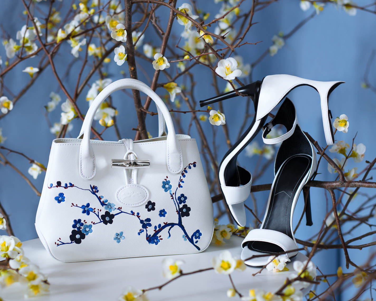 White leather handbag with high heel shoes and white flowers on a light blue background